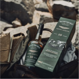 Bottle of Bowmore 10year old Whisky, with presentation box. Sat in a leather holdall outside in a rocky environment